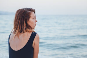 woman sitting by the ocean looking out into the distance